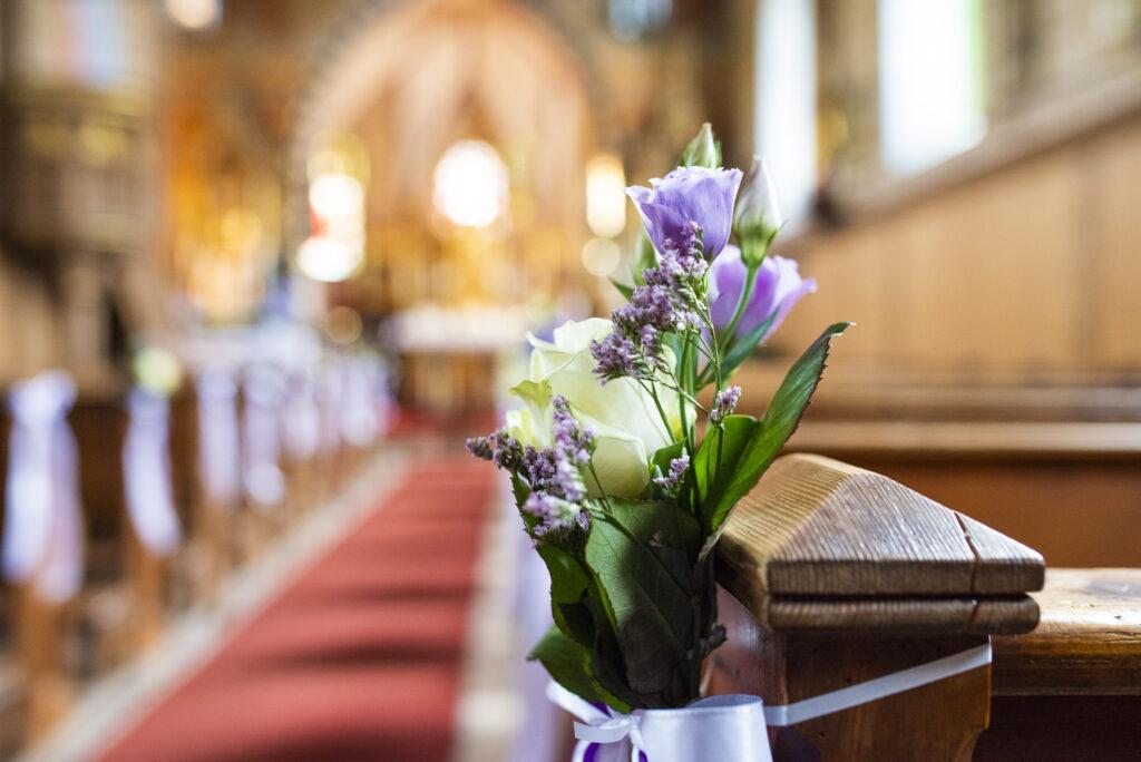 Kirchliche Trauung mit Blumen an den Bänken